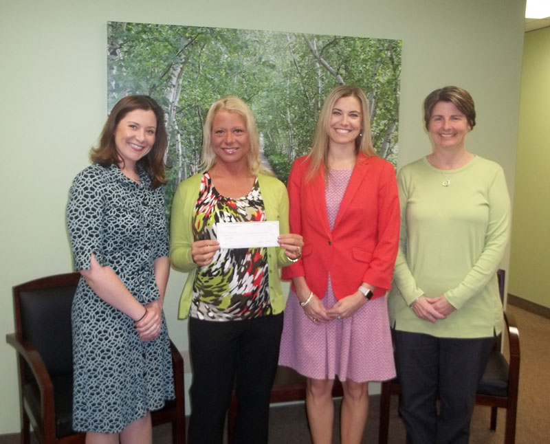 Michelle Elwood and Heather Ligus present American Heart Association with a check to support the Go Red for Women Health Expo in Cleveland, Ohio.